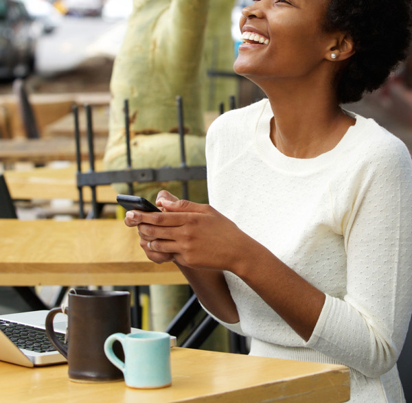 Young african woman laughing with mobile phone at cafe